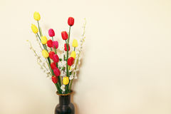 Beautiful colorful artificial flowers on concrete wall Royalty Free Stock Photo
