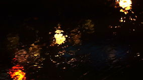 Beautiful colorful blurry light of traffic outside on the road. Rain flows and wipers on the car front windshield glass stock video
