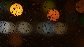 Beautiful colorful blurry light of traffic outside on the road. Rain flows and wipers on the car front windshield glass. Video of beautiful colorful blurry light stock video