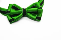 Green bow tie with black stripes. Beautiful colorful bright green bow tie with black stripes on white background with space for text as template for greeting Stock Photos