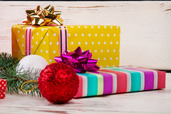 Beautiful colorful Christmas gifts with balls. Bright yellow box with polka dots and striped colored with beautiful bows. Beautiful colorful Christmas gifts Stock Image