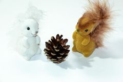 Beautiful and colorful Christmas toys to decorate a wonderful Christmas tree in the form of small forest squirrels. Brown and white hue, on a white background Royalty Free Stock Photo