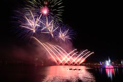 Beautiful colorful fireworks display on the urban lake for celebration on dark night background. Bright and colorful fireworks against a black night sky Royalty Free Stock Photography