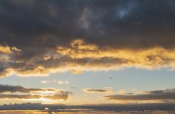 Beautiful colorful vibrant golden hour sunset skyscape with cloud formation and setting sun. Beautiful colorful golden hour sunset sky with cloud formation and stock images