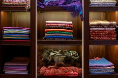 Beautiful colorful handmade pashmina shawls decorated with glittering precious stones and furs lie on the shop counters.  stock photos