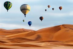 Beautiful Colorful Hot Air Baloons and dramatic clouds over the sand dunes in the desert