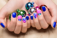 Beautiful colorful manicure with bubbles and crystals on female hand. Close-up. Royalty Free Stock Photos