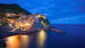 Beautiful colorful panoramic photo of village Manarola by night in Cinque Terre, Italy. Stock Images