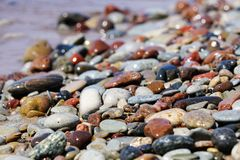 Beautiful colorful rocks on beach. Some beautiful colorful rocks on a beach. Picture has shallow depth of field. Bokeh is very nice. Color is vivid. Rocks are stock images