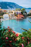 Beautiful colorful southern houses and blue bay of Mediterranean sea with some red flowers on foreground. Assos village. In Kefalonia, Greece. Vertical shot Stock Photo