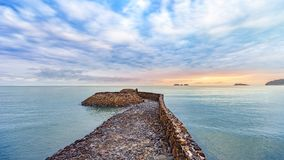 Beautiful colorful sunrise at the calmness sea shore with cloudy. Beautiful colorful sunrise at the calmness sea shore with stone bridge cloudy sky Stock Images