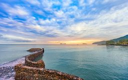 Beautiful colorful sunrise at the calmness sea shore with cloudy. Beautiful colorful sunrise at the calmness sea shore with stone bridge cloudy sky Stock Image