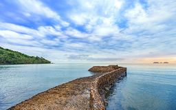 Beautiful colorful sunrise at the calmness sea shore with cloudy. Beautiful colorful sunrise at the calmness sea shore with stone bridge cloudy sky Royalty Free Stock Images