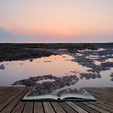 Beautiful colorful sunrise reflected in rock pools at low tide on beach coming out of pages of open story book. Beautiful vibrant sunrise reflected in rock pools stock photography