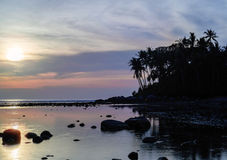 Beautiful colorful sunset near the smal eaxotic island with palm. S Royalty Free Stock Images