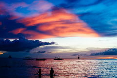 Beautiful colorful sunset over fishing boats and people in water Stock Photos