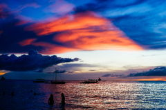 Beautiful colorful sunset over fishing boats and people in water.  Royalty Free Stock Image