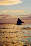 Beautiful colorful sunset over fishing boats and people in water.  Royalty Free Stock Photos