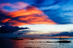 Beautiful, colorful sunset over fishing boats and people in water Stock Photos