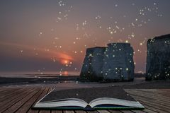 Beautiful colorful sunset over rock stacks on beach with fireflies glowing in a fantasy style image coming out of pages of open. Beautiful colorful sunset over stock photo
