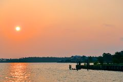 Beautiful Colorful Sunset Over the Water. With water's edge and local piers in the foreground Royalty Free Stock Photos