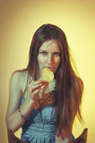 Beautiful colorful toned studio portrait of beautiful young woman sitting on the chair and eating potato chips with soulful. Emotional eyes and flowing hair on royalty free stock photos
