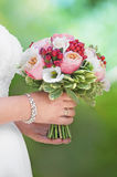 Beautiful colorful wedding bouquet in a hand of a bride Royalty Free Stock Photos