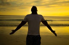 Man doing Open Arms Gesture under Setting Sun Stock Image