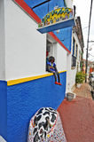 Beautiful colourful houses in Olinda. Boy sitting and checking out the street. Olinda, Recife, Pernambuco, Brazil, 2009 Stock Photos