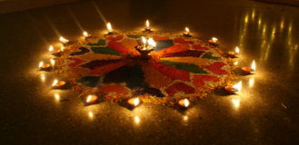Beautiful & colourful Rangoli during Diwali. Colourful Rangoli having flower like pattern, made during Diwali with beautifully lit earthen lamps Royalty Free Stock Image