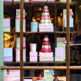 Beautiful colourful tasty macaroons cakes sweets and presents in the boxes display in window at the street shop Stock Image