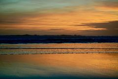 Dramatic sunset colours; beautiful sunset on a beach. Sun reflection in the water. royalty free stock images