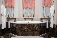Beautiful and comfortable bathroom. Beautiful and cozy bathroom against the background of pink and white curtains stock image