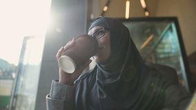 Beautiful communicative Muslim lady chatting with friends in cafe, freedom. Stock footage stock video