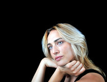 Beautiful compassionate woman on black background. Beautiful blonde haired compassionate woman on a black background with room for text Royalty Free Stock Images