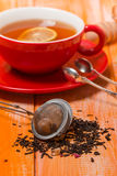 Beautiful  composition with blach tea leaves. And red cup of tea on wooden table Stock Photo