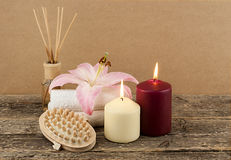 Beautiful composition with candles, spa towels and massage brush on wooden background Royalty Free Stock Images
