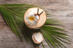 Beautiful composition with fresh green coconut. And palm leaf on wooden background Stock Images