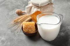 Beautiful composition with milk and honey. On grey background royalty free stock photo