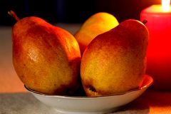 Beautiful composition with pears and candles. royalty free stock image