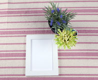 Beautiful composition with photo frames and flowers on a background of rustic rug Stock Images