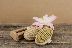 Beautiful composition with pink lily and massage brushes on wooden background Royalty Free Stock Photo