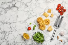 Beautiful composition with raw pasta and ingredients. For sauce on marble background, top view Stock Image