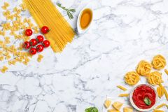 Beautiful composition with raw pasta. And ingredients for sauce on marble background, top view Stock Photo