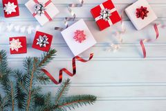 Beautiful composition, small gift boxes with bows and spirals of ribbons. A branch of the Christmas tree. Blank. Blue background, copy space royalty free stock images