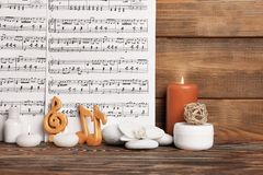 Beautiful composition of spa accessories. And musical notes on brown wooden background Royalty Free Stock Photography