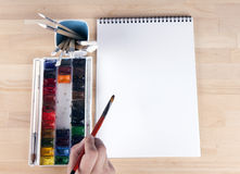 Beautiful composition of watercolor paints, brushes, album artist, with the artist's hand Royalty Free Stock Image