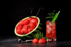 A beautiful composition of watermelon products on a black background. Red watermelon scoops and sweet berry beverage Stock Images