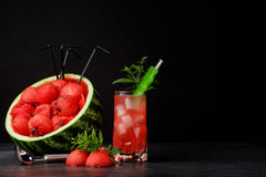 A beautiful composition of watermelon products on a black background. Red watermelon and sweet berry drink with mint Stock Image