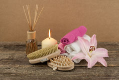 Beautiful composition with white candle, aromatic oil and massage brushes on wooden background. Body and ckin care concept royalty free stock images